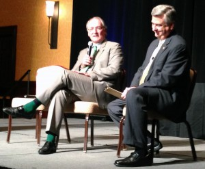Jack Swarbrick (left) speaks with Jack Nolan (right) at the Shamrock Series luncheon while showing off a seriously on-point sock game.